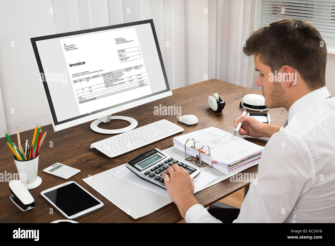 Male Accountant Calculating Tax In Front Of Computer At Desk Stock Photo -  Alamy