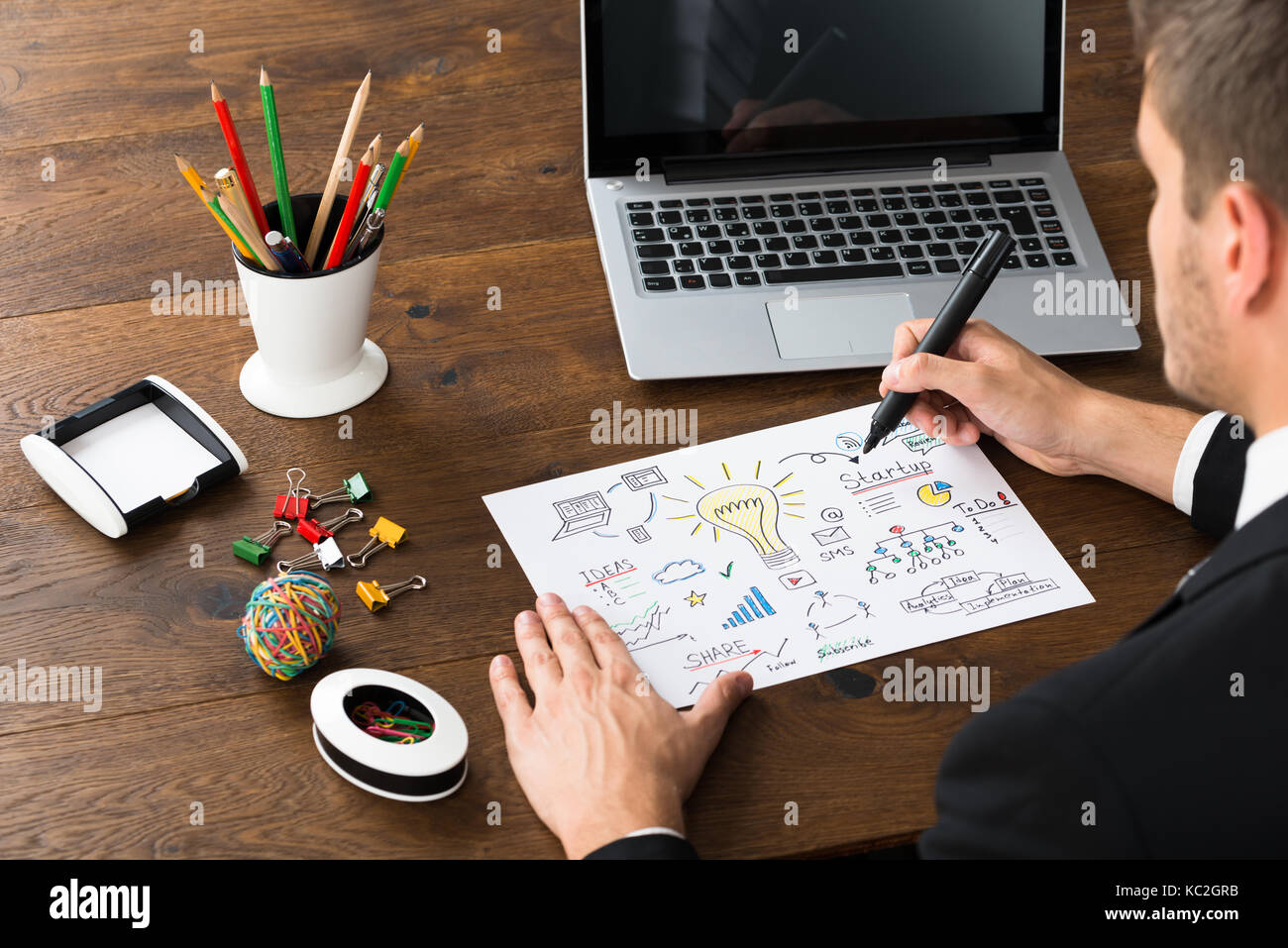 close-up of businessman with office supplies and laptop drawing diagram of  start-up plan at desk