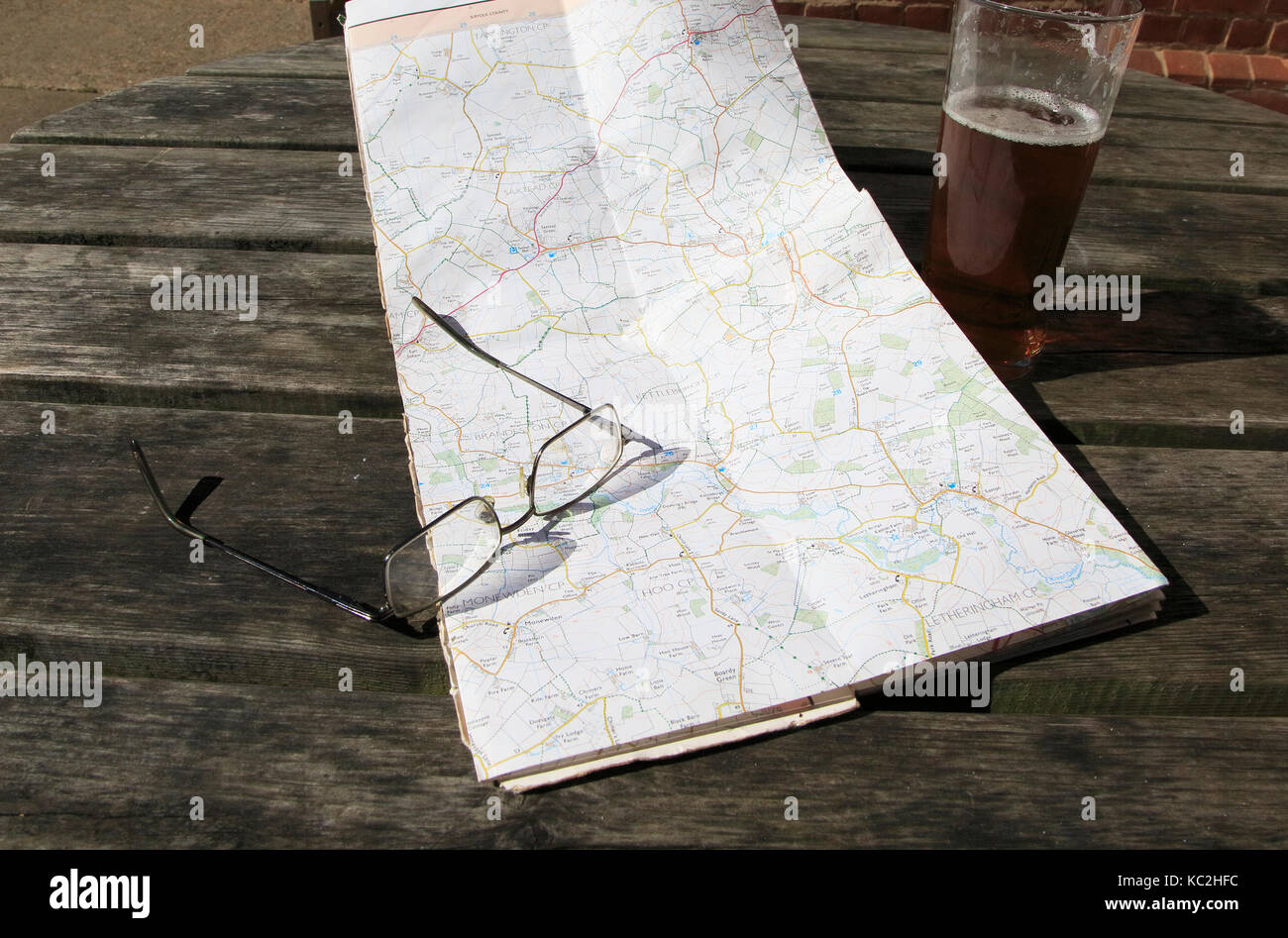 Ordnance Survey Explorer map opened on table with spectacles and pint glass of beer, Suffolk, England, UK - Stock Image