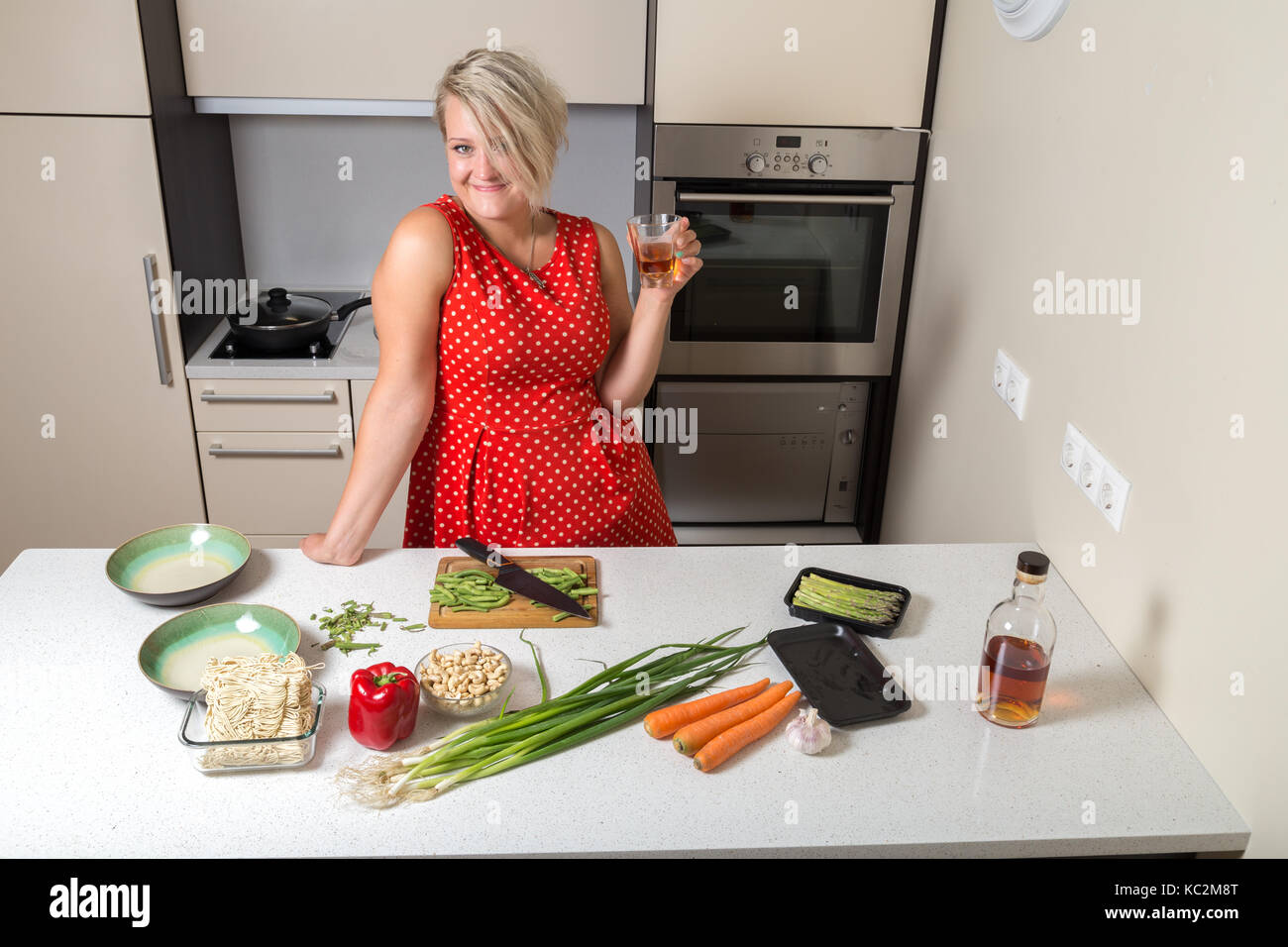 Adult girl holding whiskey glass in hand and smiling Stock Photo