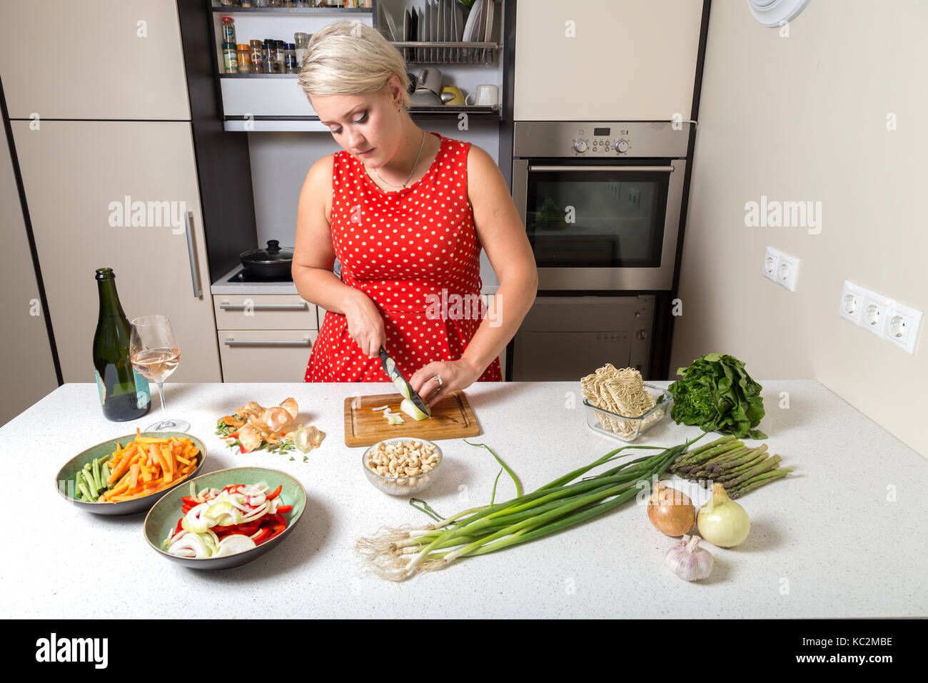Girl cutting onions in red dotted dress Stock Photo