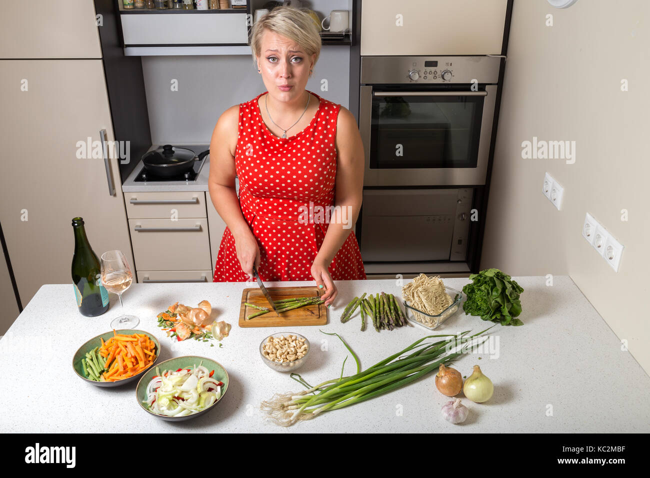 Surprised young woman in kitchen cutting asparagus Stock Photo