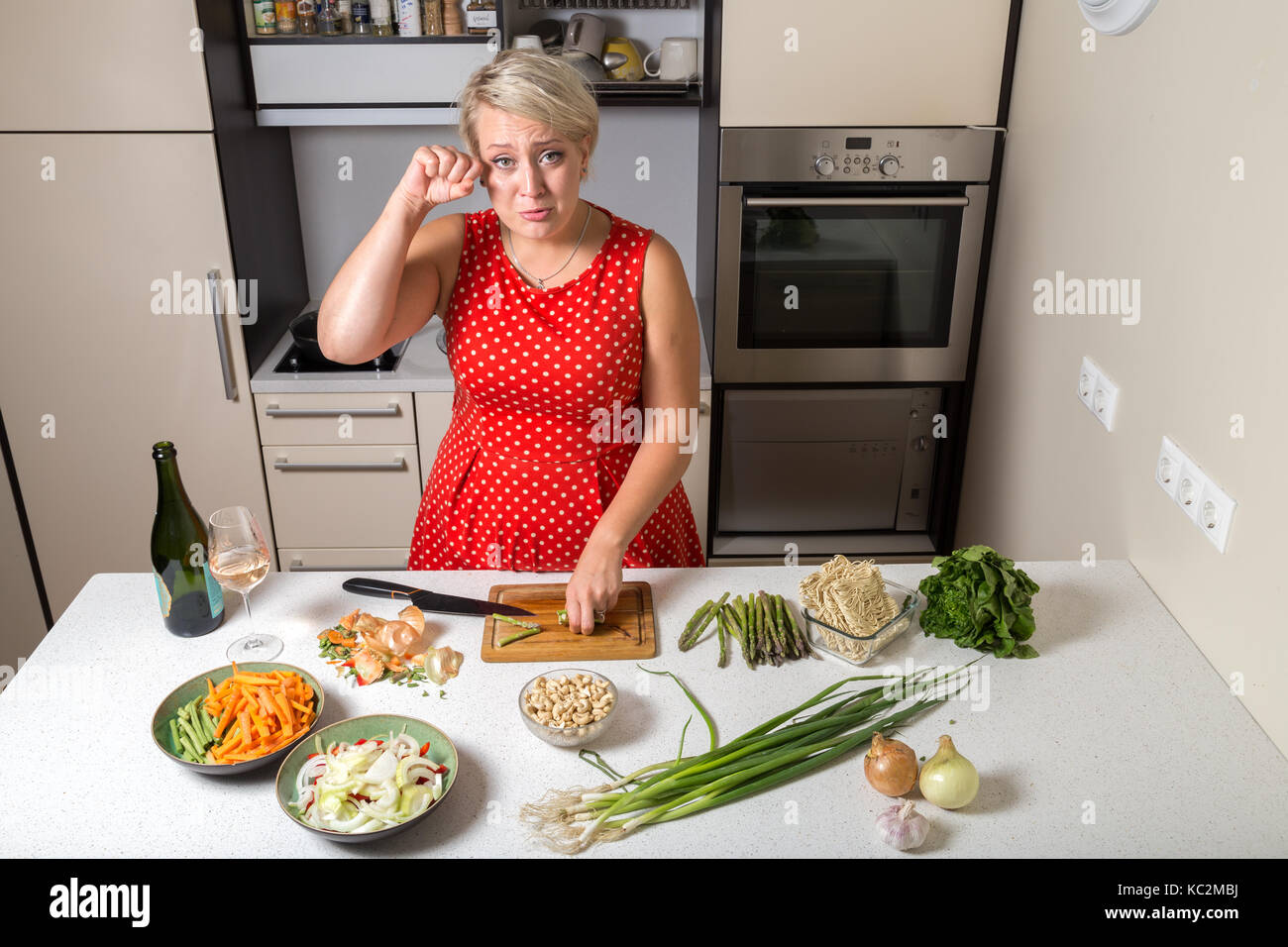 Female in kitchen cutting asparagus and rubbing her eye Stock Photo