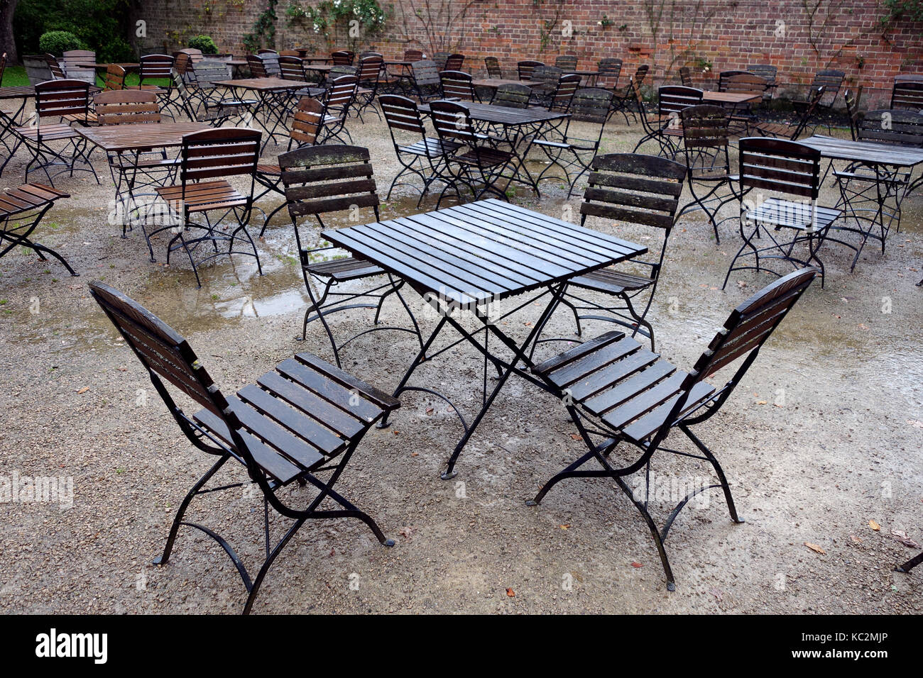 Empty wet tables and chairs at rained off garden party - Stock Image