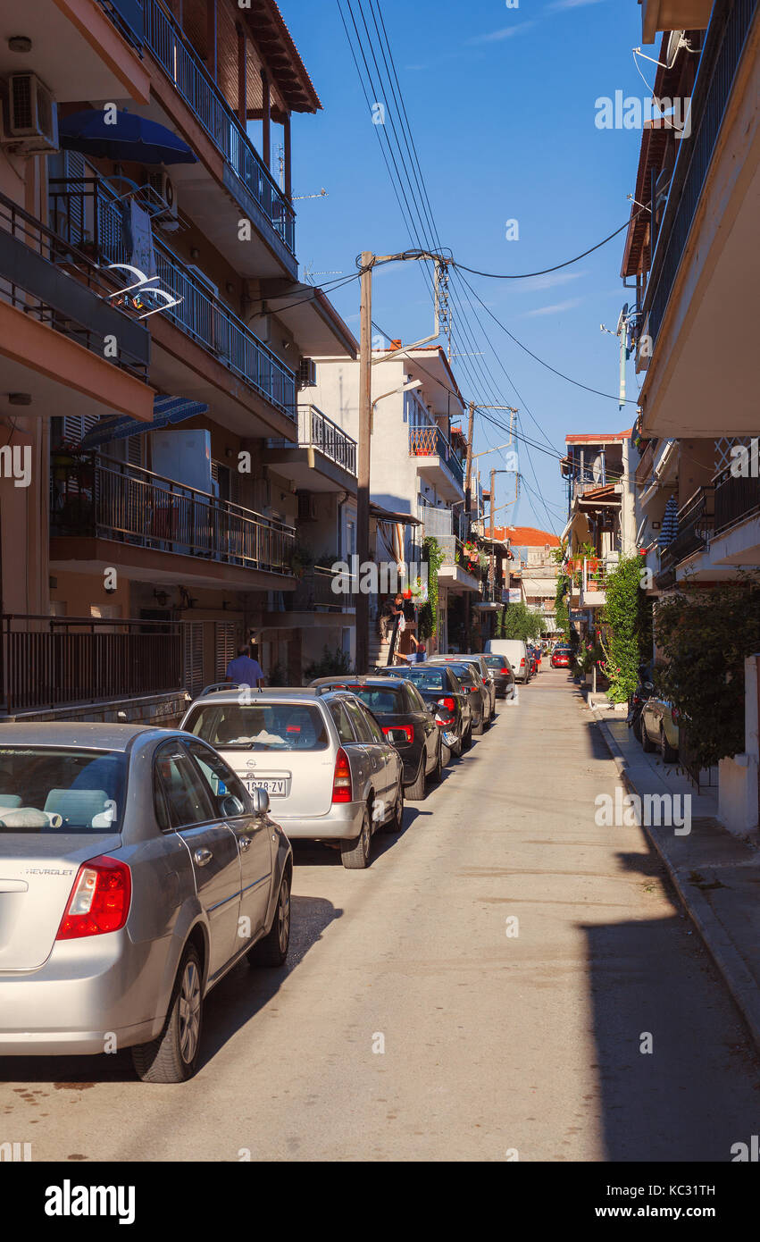 Stavros, Greece - September 04, 2017: One ordinary street during day, apartments and houses for rent. - Stock Image