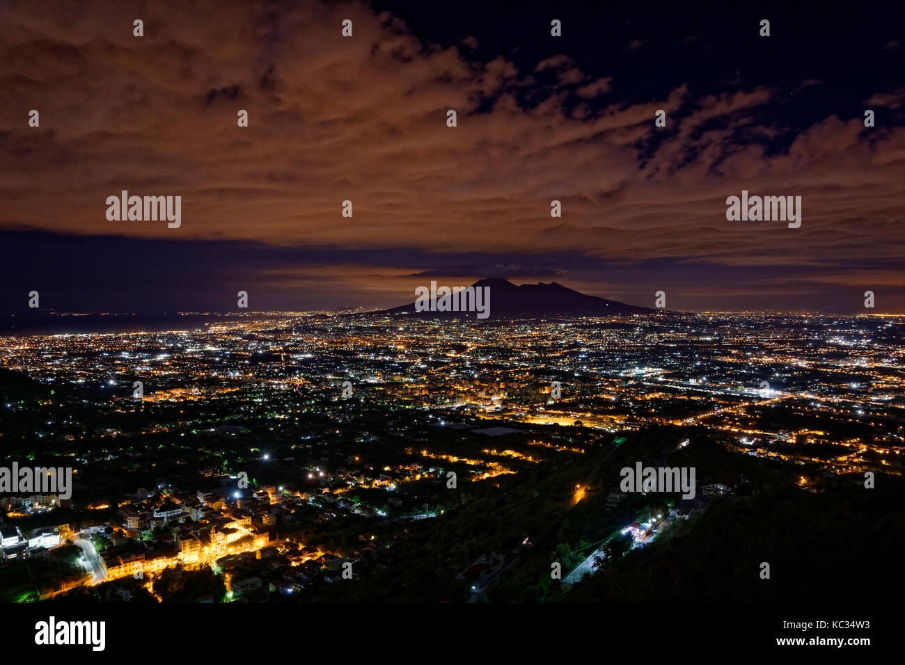 Mount Vesuvius silhouetted by the glow from the Naples conurbation in Campania Province, Southern Italy. - Stock Image