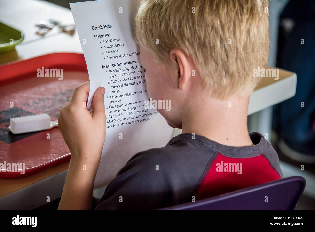 Young blind child reading paper up close - Stock Image