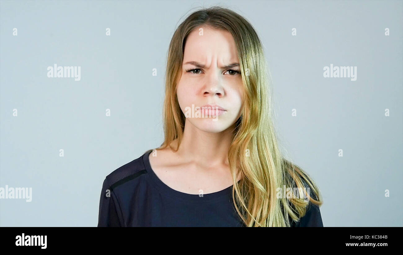 Young beautiful woman is angry on a white background. Angry young woman - Stock Image