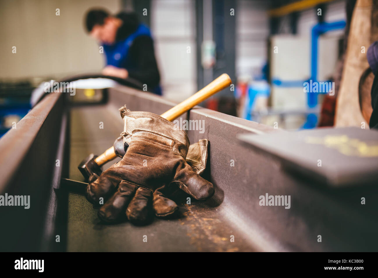 Protective gloves and hammer in the metal profile background Stock Photo
