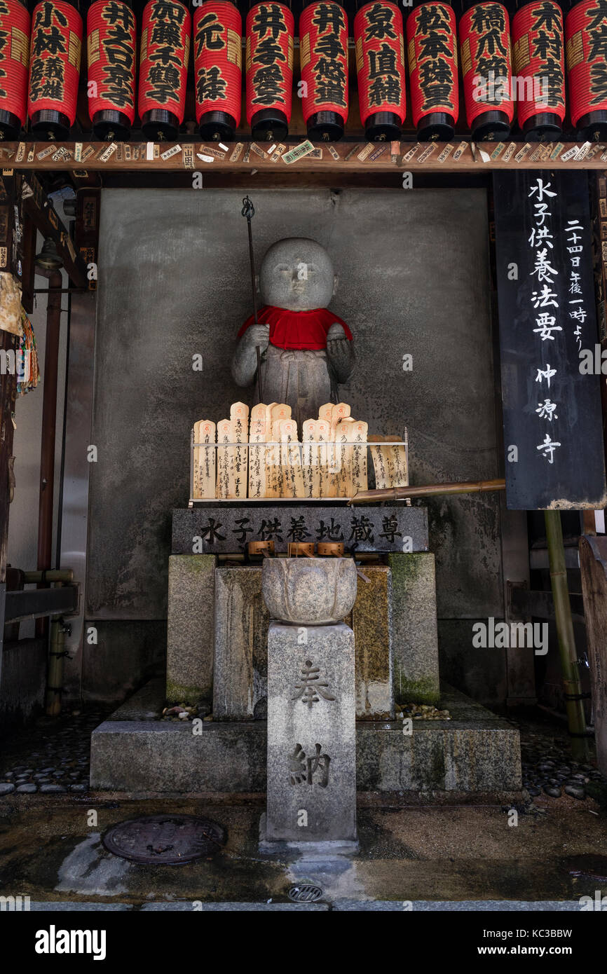 Kyoto - Japan, May 18, 2017: Traditional stone carved Jizo and red lanterns for praying and wishing - Stock Image