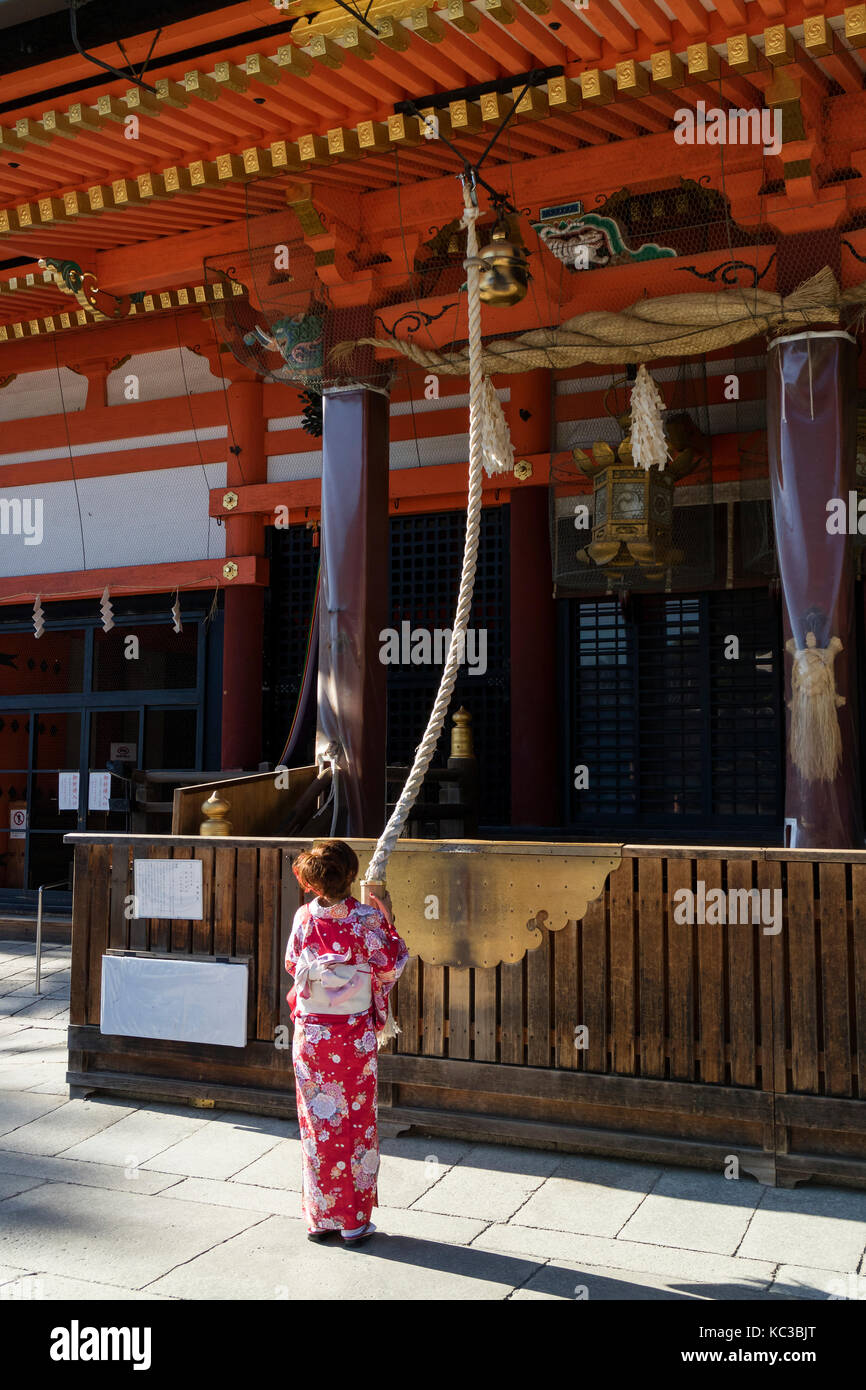 Kyoto, Japan - May 18, 2017: Woman in kimono pulling the bell-rope as a sign of devotion at the Yasaka jinja shrine - Stock Image