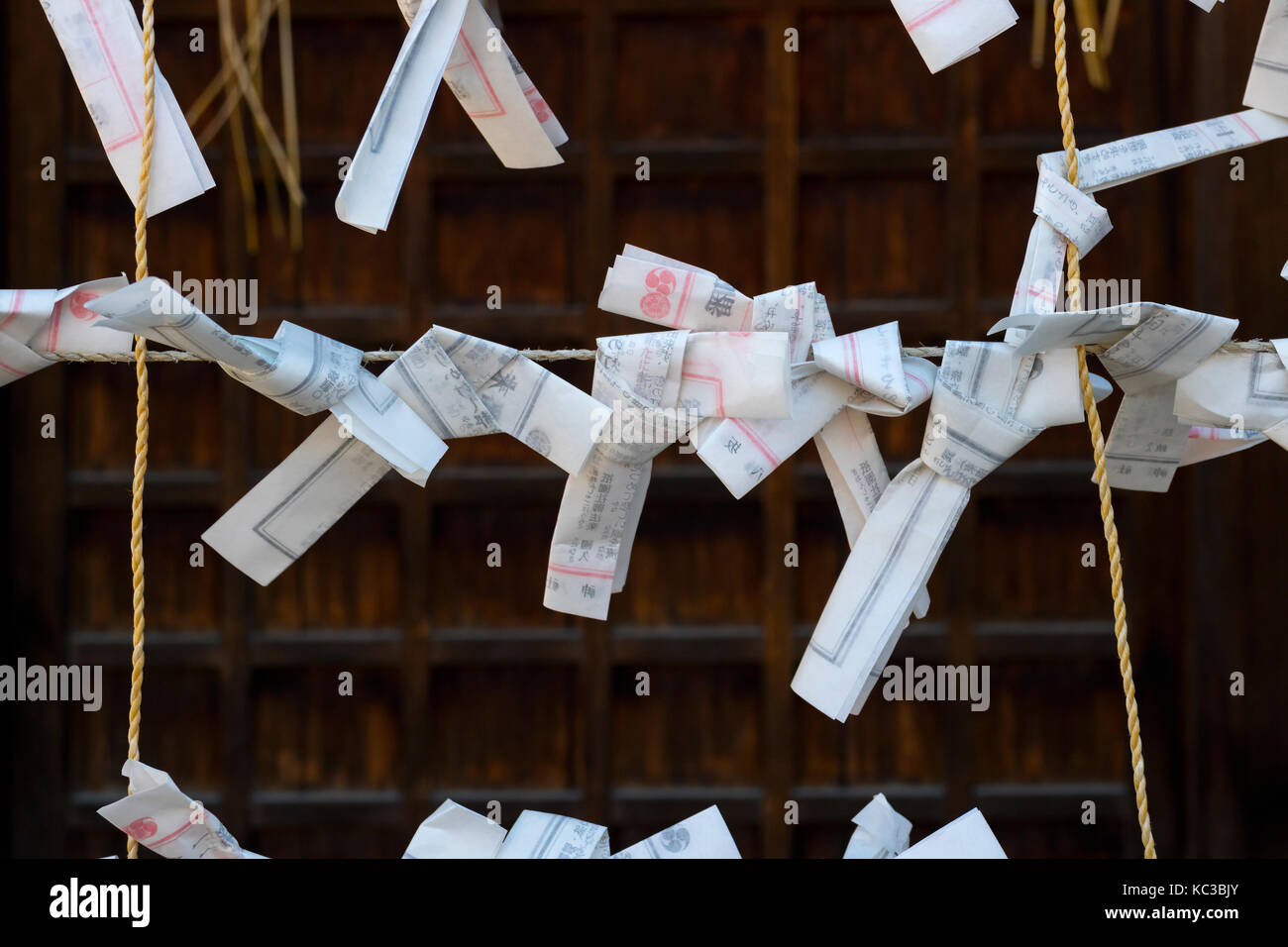 Kyoto, Japan - May 18, 2017: Paper prayers and wishes tied on a rope at the Yasaka jinja shrine in Kyoto - Stock Image