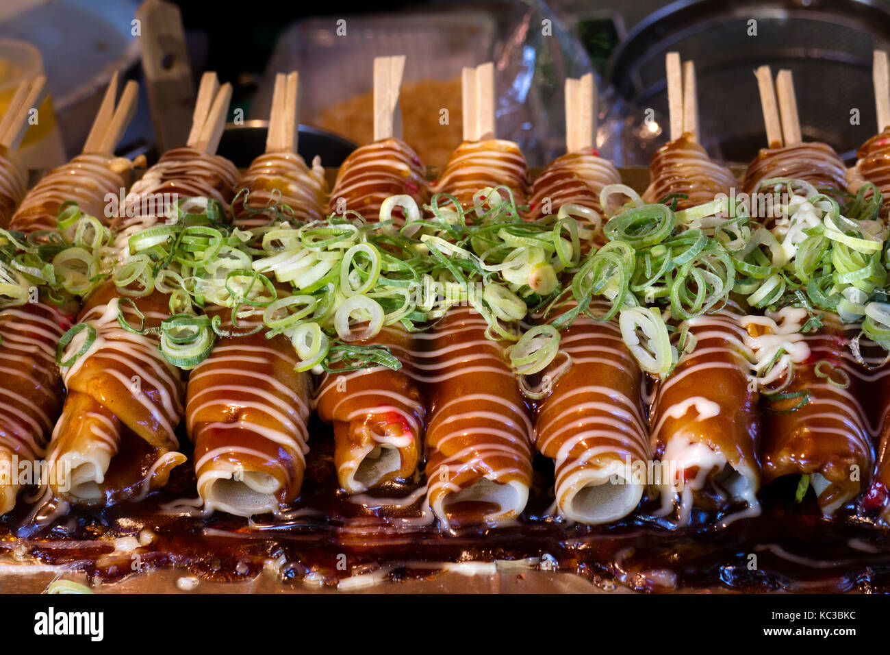 Kyoto, Japan - May 18, 2017: Baking Hashimaki,  okonomiyaki on sticks with fresh spring onions as a snack - Stock Image