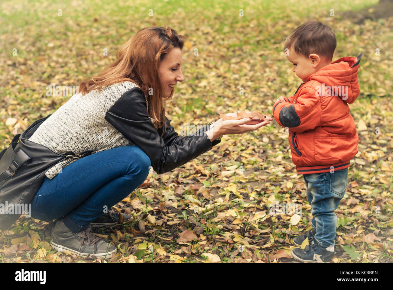 Mom and her young son playing in the park, autumn moments - Stock Image