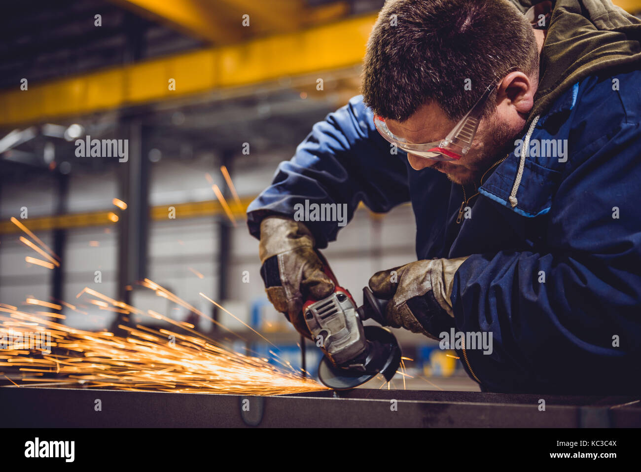 Worker Using Angle Grinder in Factory and throwing sparks - Stock Image