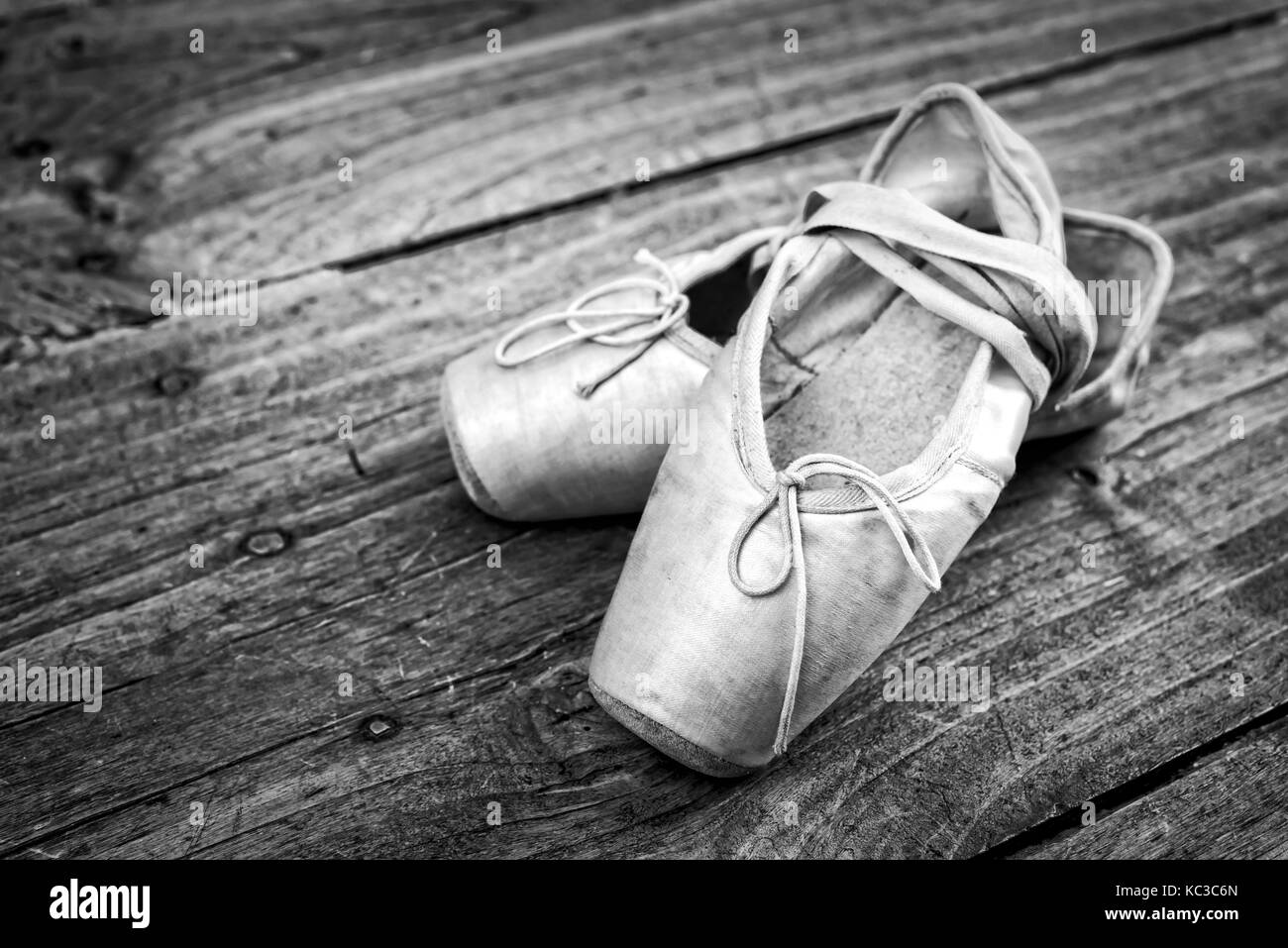 Old pink ballet shoes on a wooden floor, vintage process - Stock Image