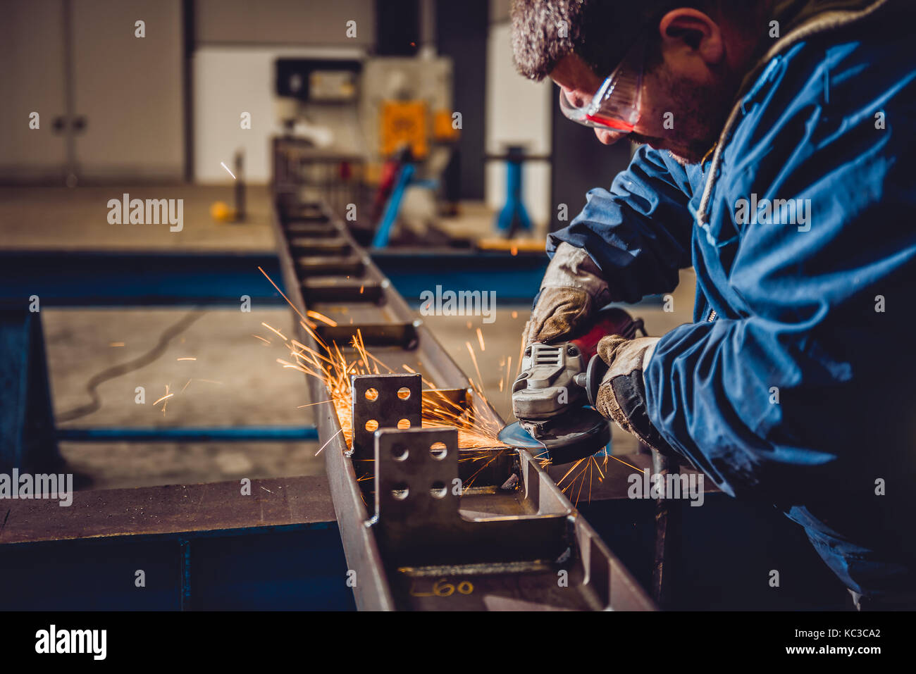 Worker Using Angle Grinder in Factory and throwing sparks Stock Photo