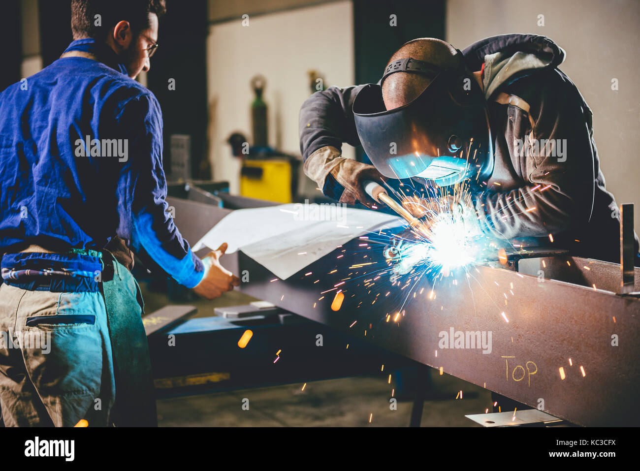 Industrial Welder With Torch and Protective Helmet in big hall welding metal profiles and in the background engineer - Stock Image