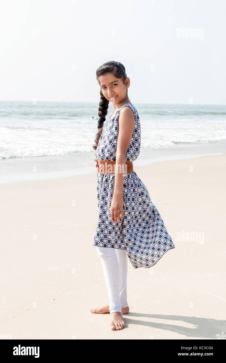 Portrait Of Beautiful Indian Teenage Female Wearing In A Dress On The Beach In Sunlight