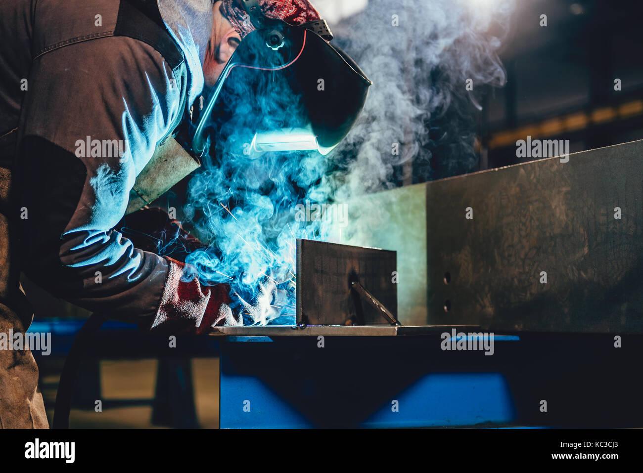 Industrial Welder With Torch and Protective Helmet in big hall welding metal profiles - Stock Image