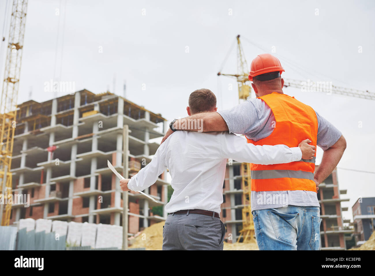 construction, architecture, business, teamwork and people concept - happy architects with blueprint at building - Stock Image