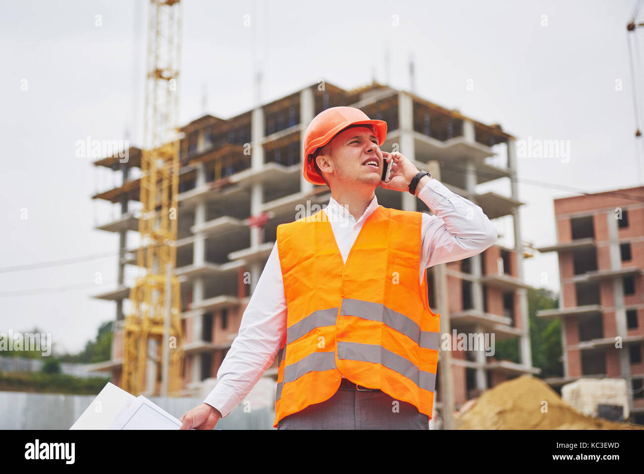 Young architect wearing a protective helmet standing on the mountains building outdoor background - Stock Image