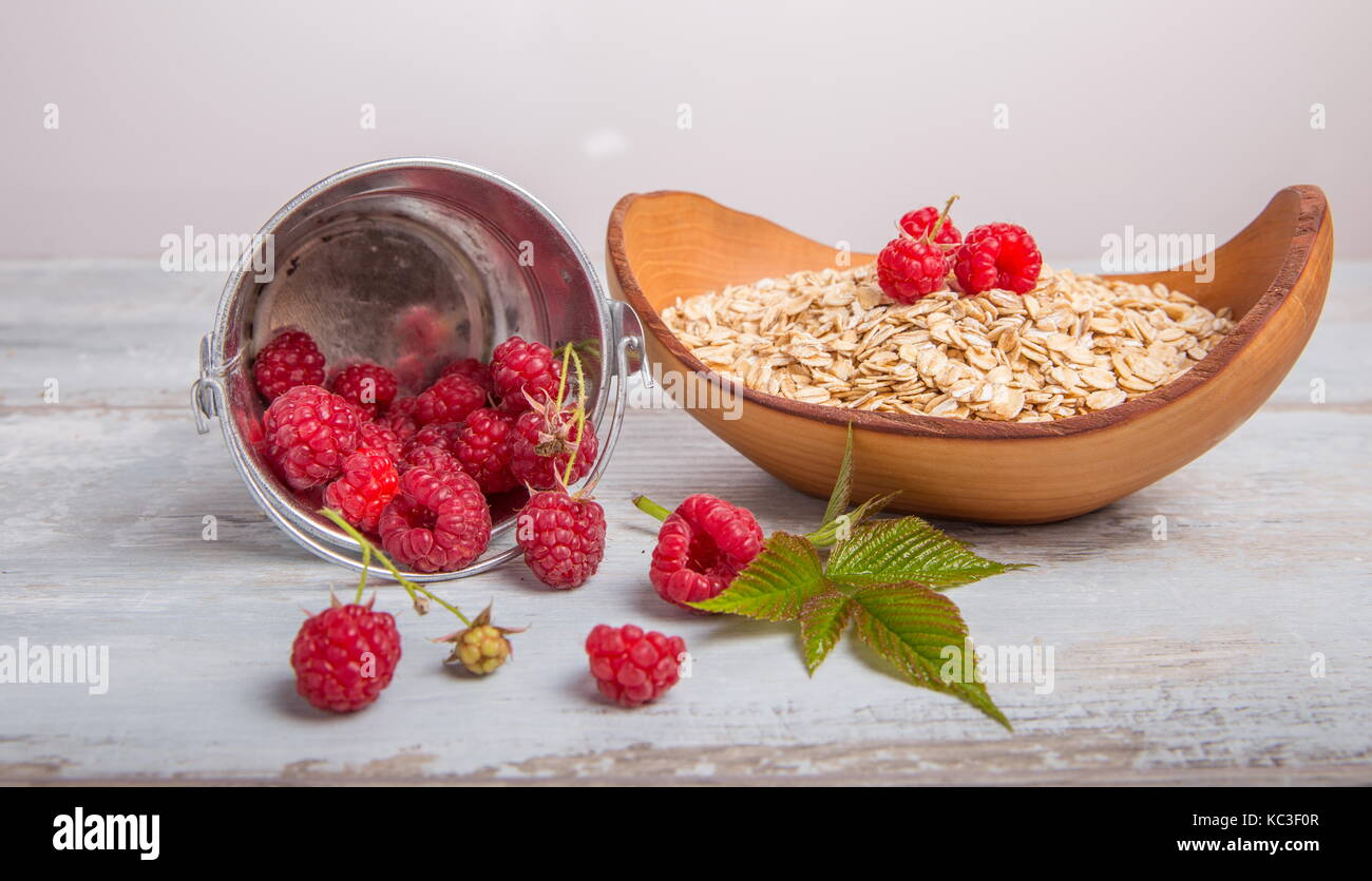 Fresh raspberries in a bucket and oat flakes in a wooden bowl on a rustic wooden background. Healthy diet, vegetarian - Stock Image