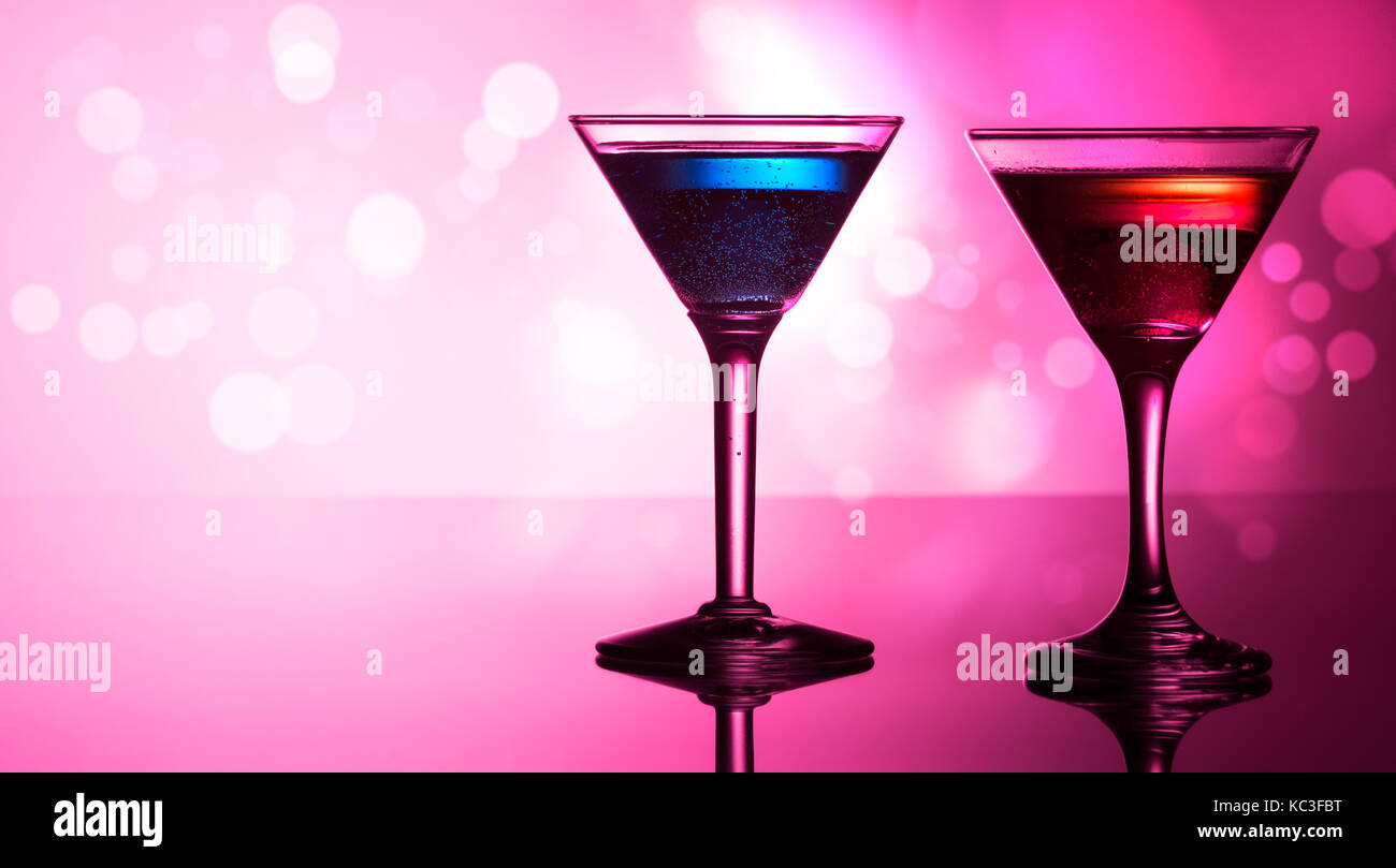 Colorful cocktails on reflective top, with bokeh background - Stock Image