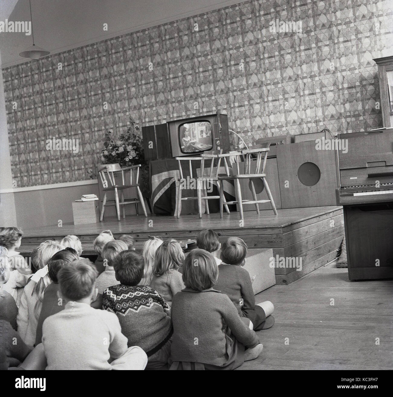 1964, historical, group of primary school children sit together watching a childrens programme on a new television - Stock Image