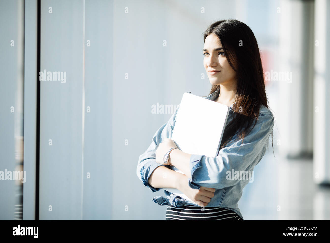 Successful female office worker with net-book is standing in skyscraper interior against big window with city view - Stock Image