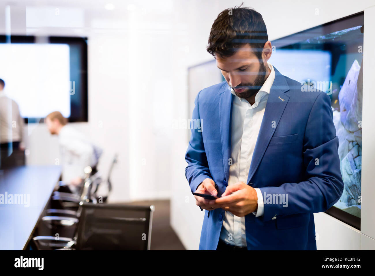 Portrait of young businessman using mobile phone - Stock Image