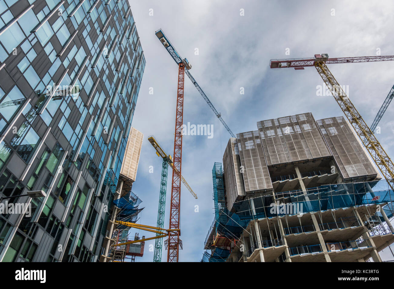 Skyward view of construction at Greenwich Peninsular in East London, with new build apartment blocks and cranes. - Stock Image