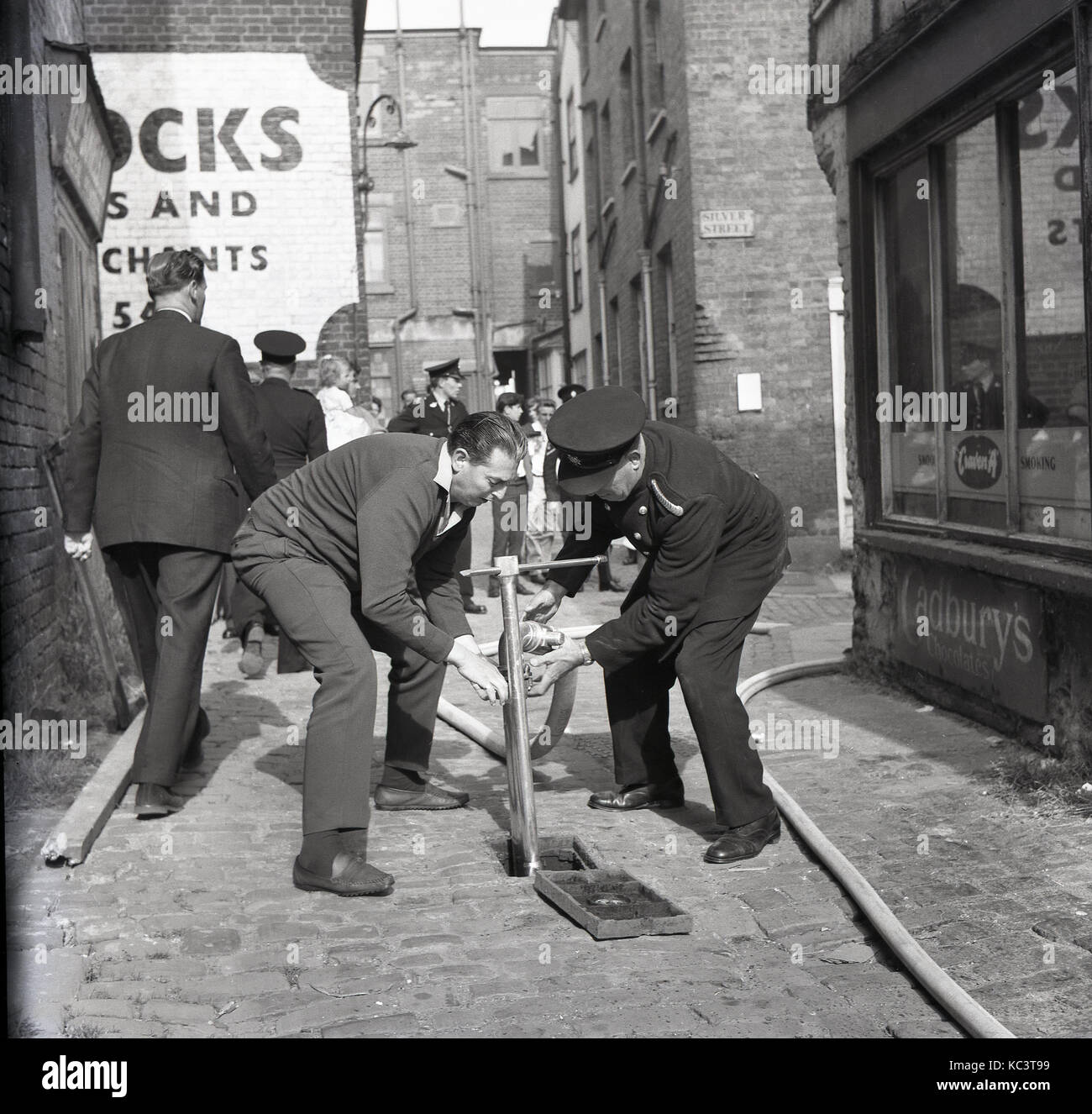1964, historical, picture shows a fireman and adult male helper trying to put a hosepipe onto a mains water supply - Stock Image