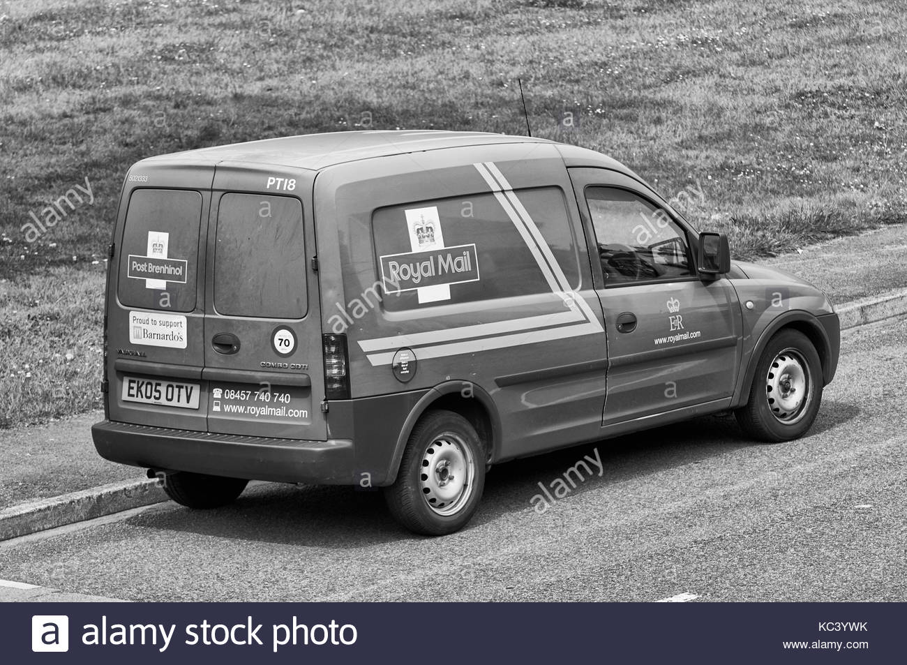 A red post office royal mail van parked at the roadside - Stock Image