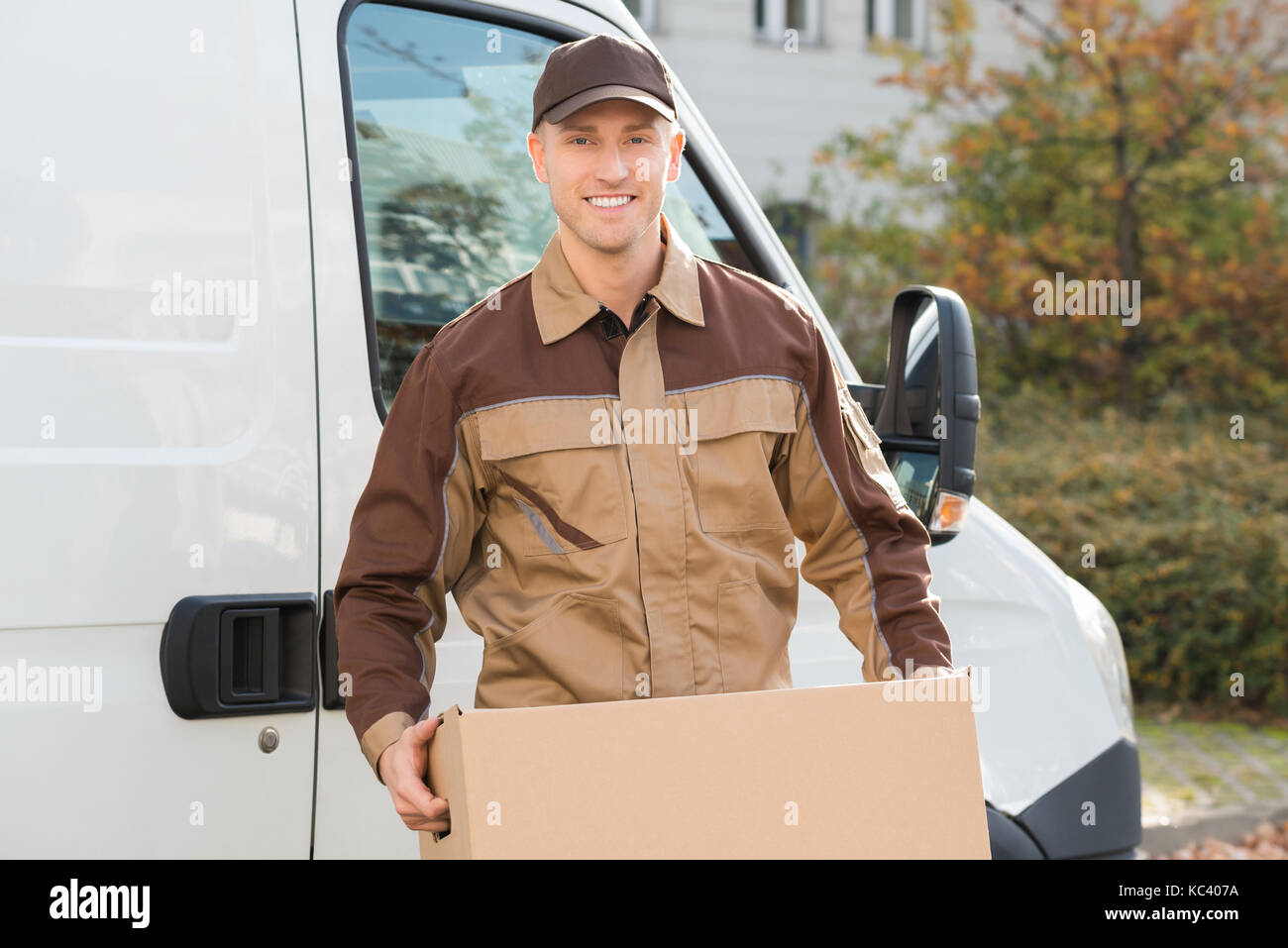 Portrait of young delivery man carrying cardboard box with truck in background - Stock Image
