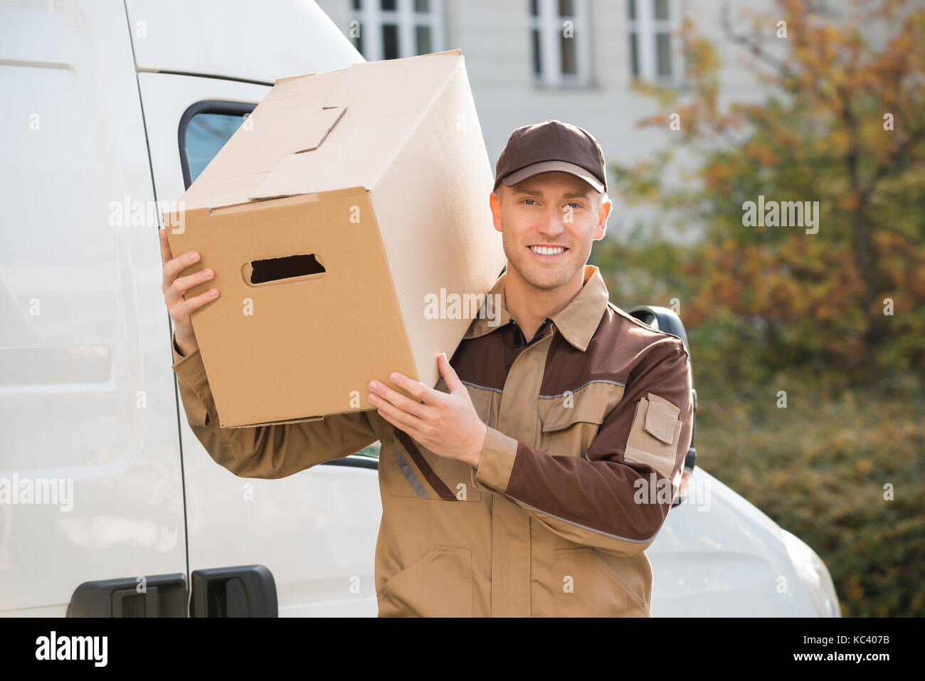 Portrait of young delivery man carrying cardboard box on shoulder with truck in background - Stock Image