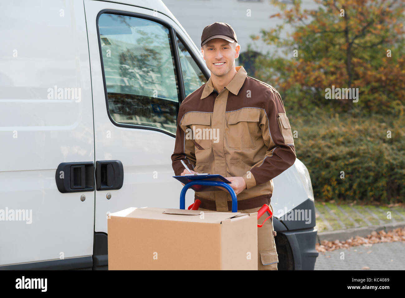 Portrait of confident delivery man with parcels and clipboard standing on street - Stock Image