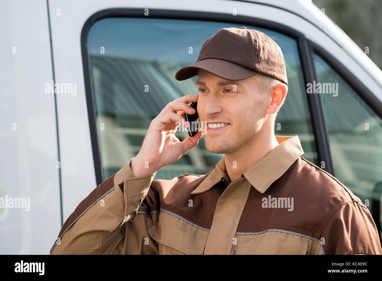 Portrait of smiling delivery man using mobile phone against truck - Stock Image