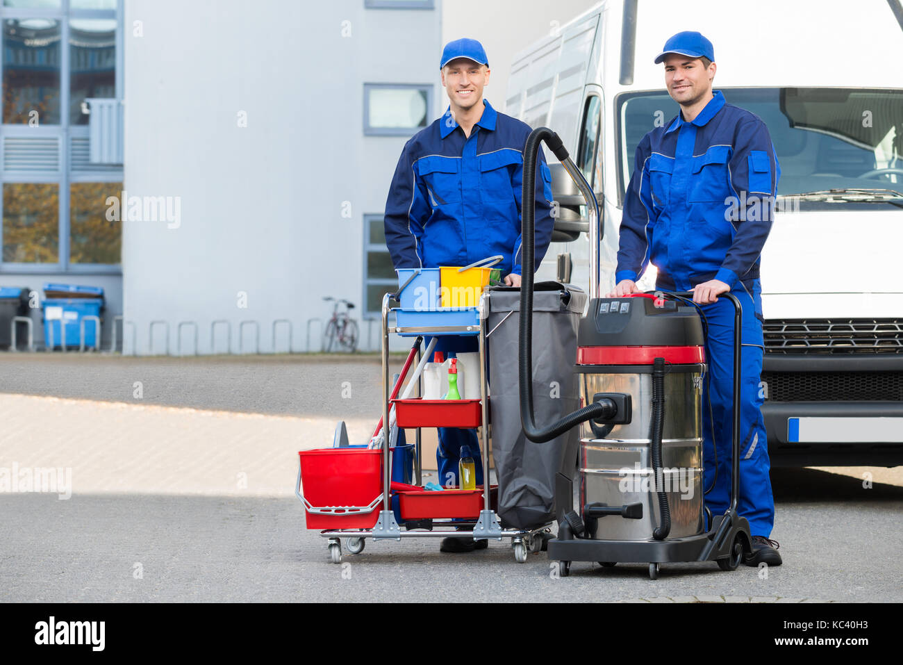 Portrait of confident male janitors with cleaning equipment standing on street Stock Photo