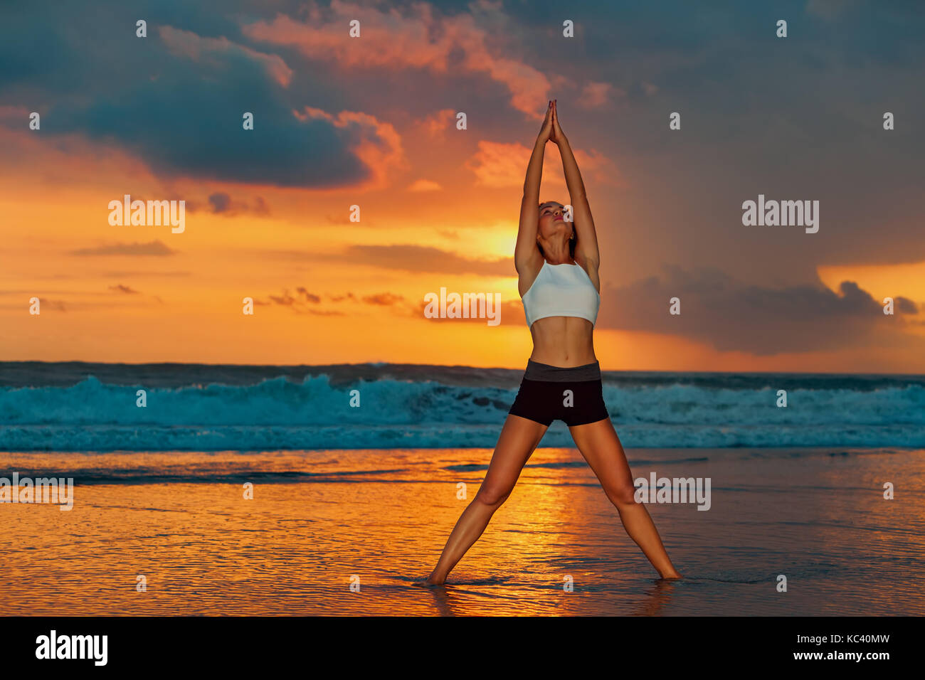 Meditation on sunset sky background. Active woman in yoga pose on sea beach, stretching to keep fit and health. - Stock Image