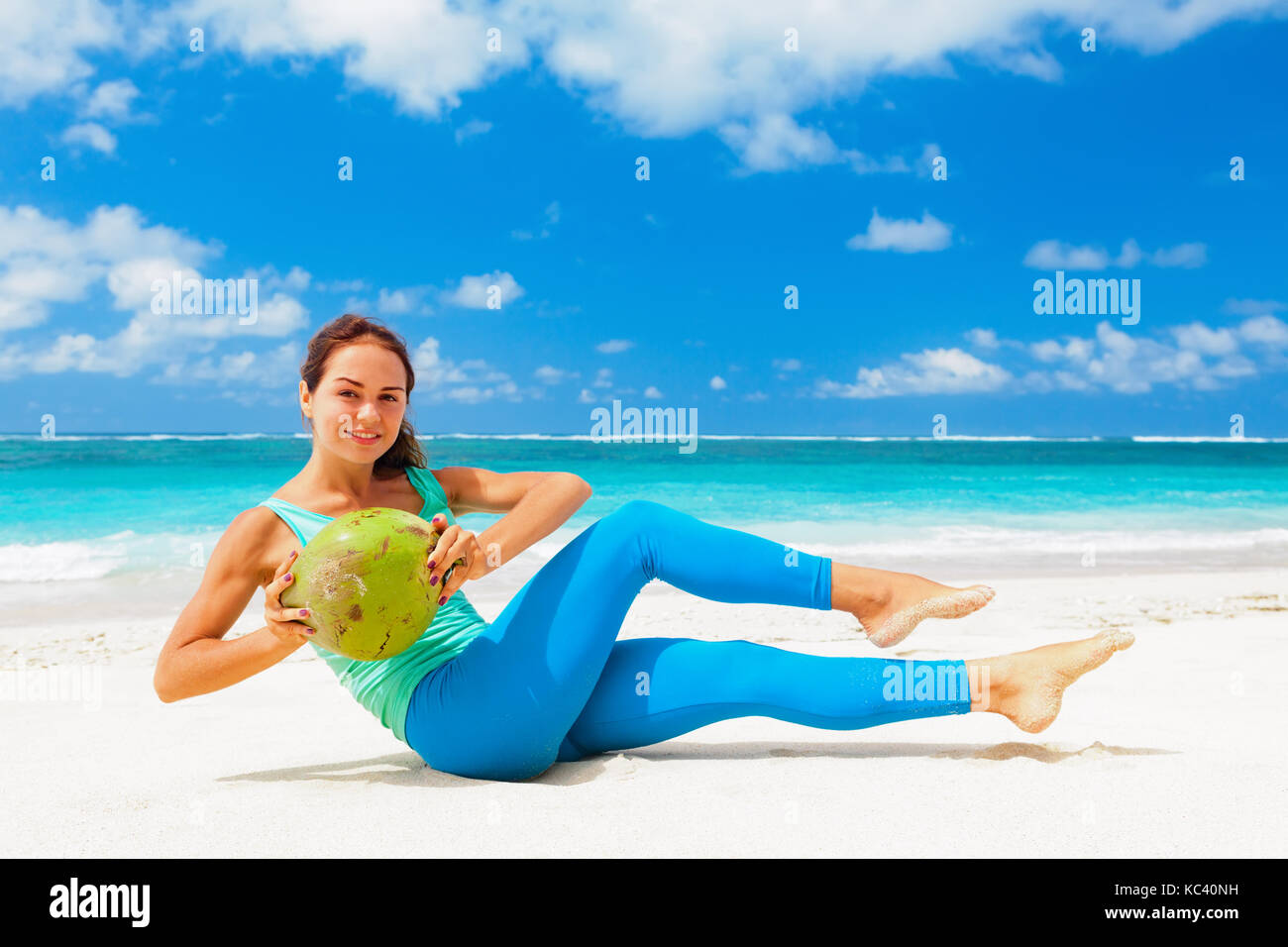 Young woman fitness abdominal exercise on beach to keep fit and health. Doing crunches core, leg raising and twisting - Stock Image