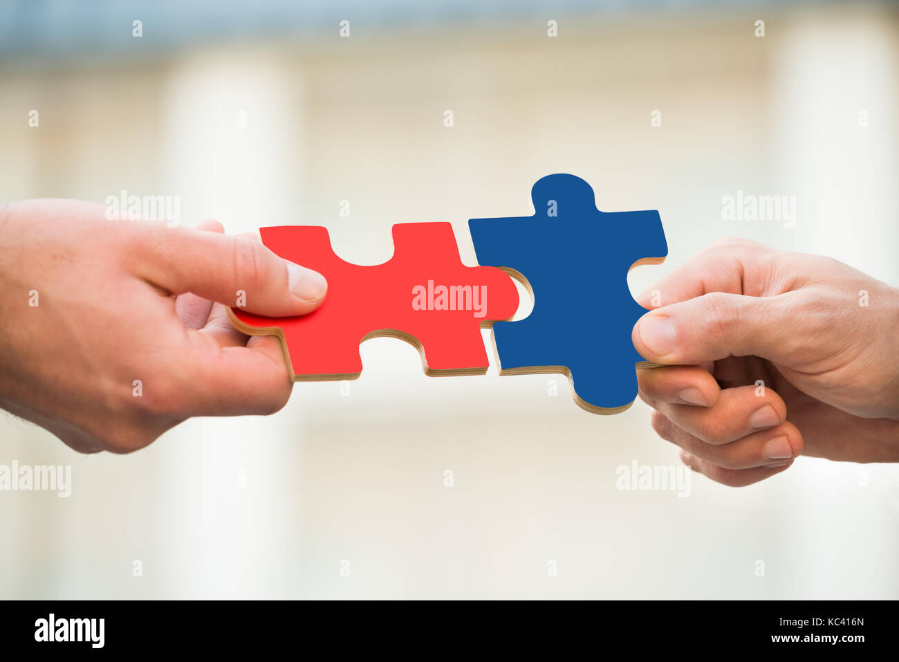 Cropped hands of businessmen joining jigsaw pieces outdoors - Stock Image