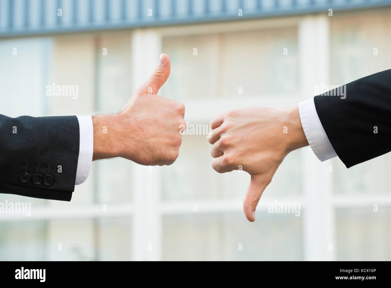 Cropped hands of businessmen showing like and dislike signs outdoors - Stock Image