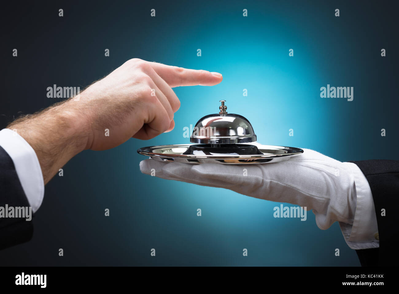 Cropped image of businessman ringing in service bell held by bellboy against blue background - Stock Image