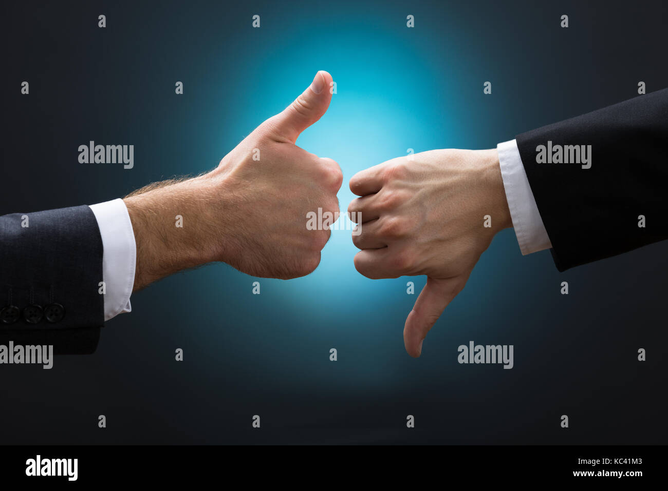 Cropped hands of businessmen showing like and dislike signs against blue background - Stock Image