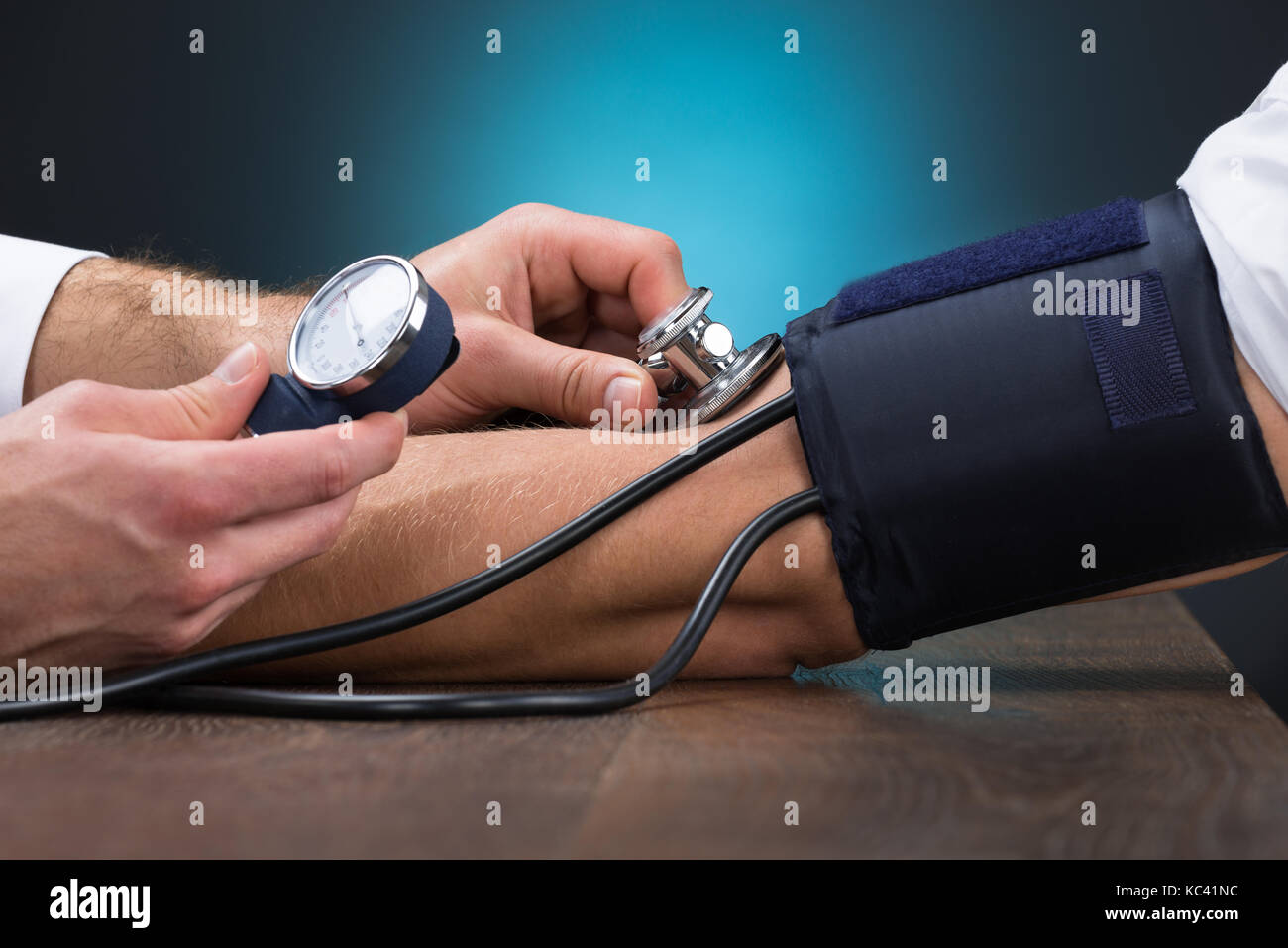Cropped image of male doctor checking blood pressure of patient at table - Stock Image
