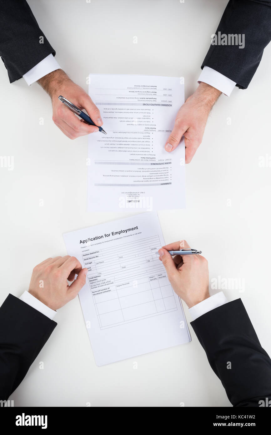 Cropped image of businessman taking interview of male candidate at desk - Stock Image