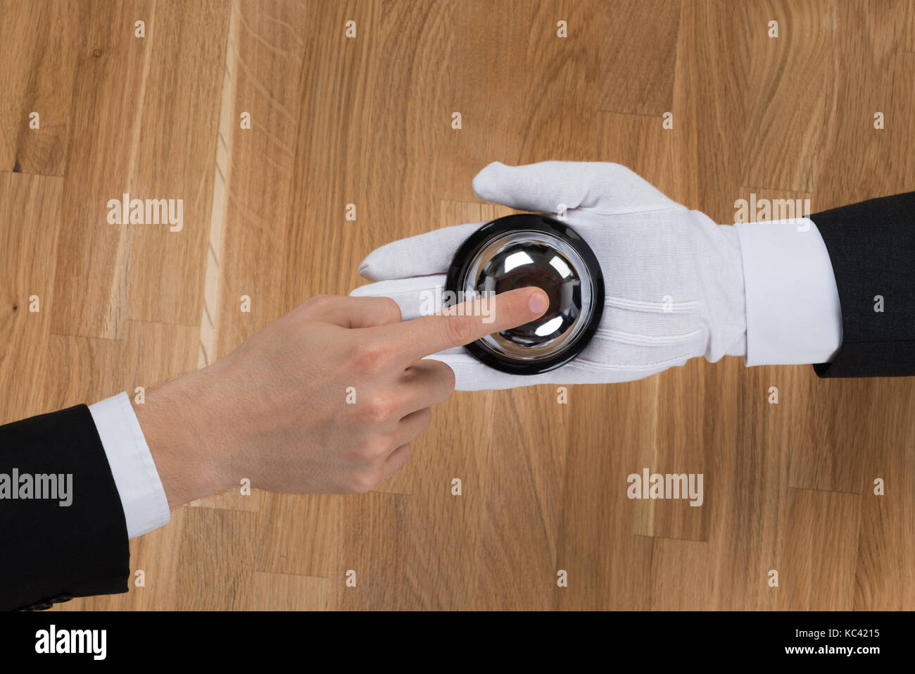 Cropped image of businessman ringing in service bell held by bellboy at reception counter - Stock Image