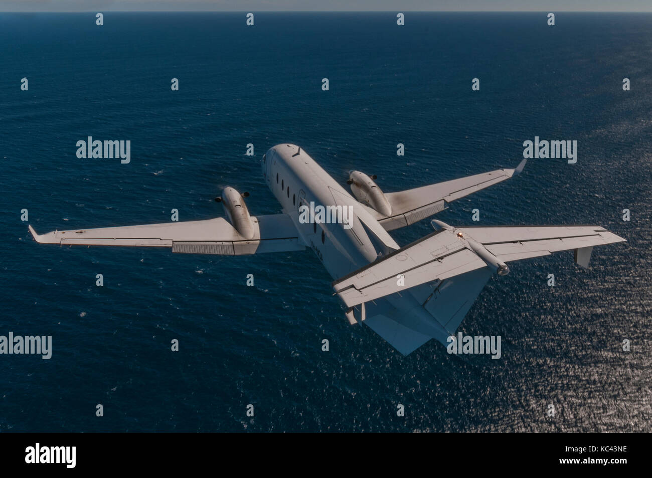 An air-to-air, rear end portrait of a Raytheon Beechcraft B1900D aircraft in flight over the ocean. - Stock Image