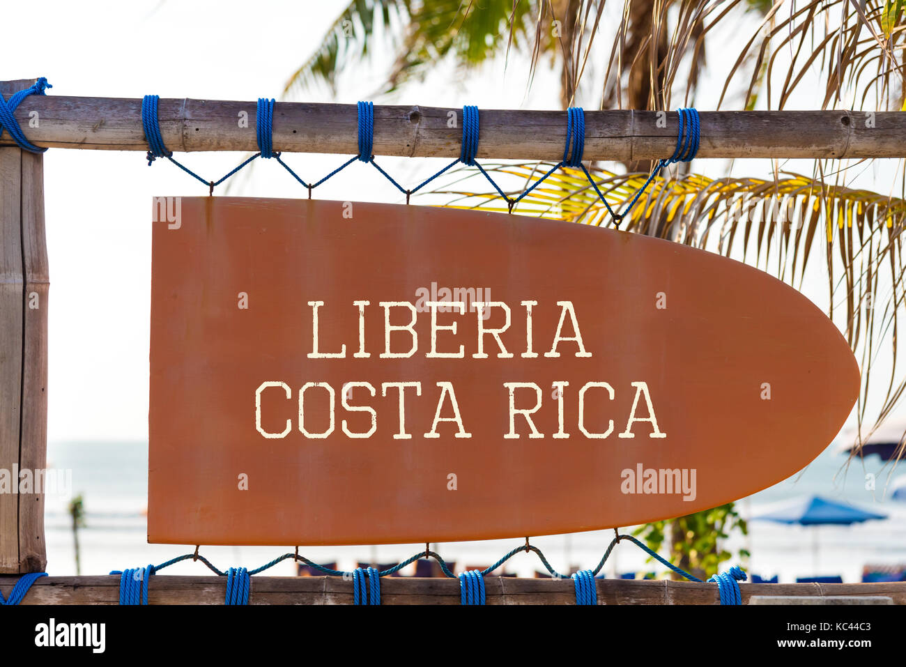 Orange vintage signboard in shape of surfboard with Liberia, Costa Rica text for surf spot and palm tree in background. - Stock Image